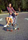 Two happy beautiful teen girls driving shopping cart outdoors Stock Photos