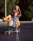 Two happy beautiful teen girls driving shopping cart outdoors Stock Images