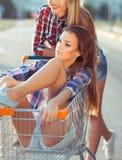 Two happy beautiful teen girls driving shopping cart outdoors Royalty Free Stock Photo