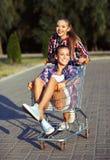 Two happy beautiful teen girls driving shopping cart outdoors Stock Image