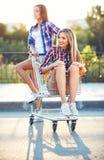 Two happy beautiful teen girls driving shopping cart outdoors Stock Photo