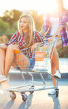 Two happy beautiful teen girls driving shopping cart outdoors Royalty Free Stock Photography