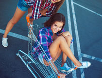 Two happy beautiful teen girls driving shopping cart outdoors Stock Image