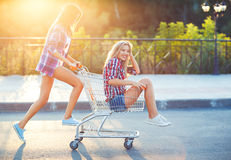 Two happy beautiful teen girls driving shopping cart outdoors Royalty Free Stock Images