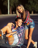 Two happy beautiful teen girls driving shopping cart outdoors Stock Photography