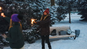 Two Happy beautiful Teen Girls having fun with sparklers in winter holidays. Two young beautiful girls whirls and jumps with sparklers on the snowy ground in stock footage