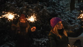 Two Happy beautiful Teen Girls having fun with sparklers in winter holidays. Two young beautiful girls whirls and jumps with sparklers on the snowy ground in stock video