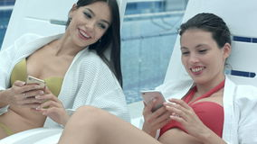 Two happy beautiful women lying on poolside chaise longues and showing each other photos from their phones stock footage