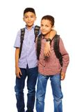 Team of two brothers. Two happy black brothers standing together with backpack hugging, portrait isolated on white stock photos