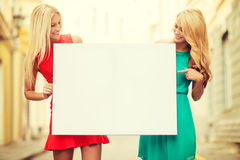 Two happy blonde women with blank white board Stock Image