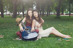 Two happy boho chic stylish girlfriends with guitar, picnic stock image