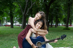 Two happy boho chic stylish girlfriends with guitar, picnic stock images