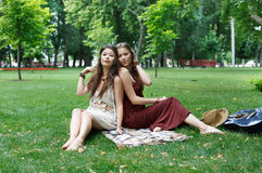 Two happy boho chic stylish girlfriends picnic in park. Fancy girls have picnic in park on grass. Modern hippie boho style Stock Image