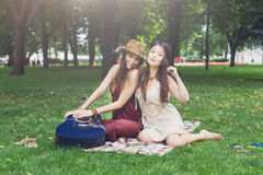 Two happy boho chic stylish girlfriends picnic in park. Fancy girls have picnic in park on grass. Modern hippie boho style Royalty Free Stock Image