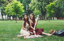 Two happy boho chic stylish girlfriends picnic in park. Fancy boho girls have picnic in park on grass. Modern hippie style Stock Images