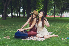 Two happy boho chic stylish girlfriends picnic in park. Fancy girls have picnic in park on grass. Modern hippie boho style Royalty Free Stock Images