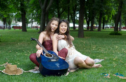 Two happy boho chic stylish girlfriends picnic in park. Fancy girls musicians have picnic in park on grass. Modern hippie boho style Stock Photo