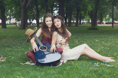 Two happy boho chic stylish girlfriends picnic in park. Fancy girls musicians have picnic in park on grass. Modern hippie boho style Stock Photos