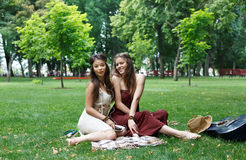 Two happy boho chic stylish girlfriends picnic in park. Young girls outdoors on the grass at summer sunny day. Women listen music in earphones together, sit at Stock Photos