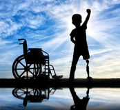 Two happy boy with a disability. Children& x27;s disability concept. Two happy boy with a disability with a prosthetic leg standing near a wheelchair at the Stock Photo