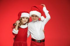 Two happy boy and girl in santa claus hats with gift boxes at studio. Two happy boy and girl in santa claus hats with gift boxes at red studio Stock Photos