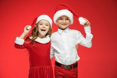 Two happy boy and girl in santa claus hats with gift boxes at studio. Two happy boy and girl in santa claus hats with gift boxes at red studio Royalty Free Stock Photos