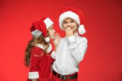 Two happy boy and girl in santa claus hats with gift boxes at studio. Two happy boy and girl in santa claus hats with gift boxes at red studio Royalty Free Stock Photo