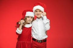 Two happy boy and girl in santa claus hats with gift boxes at studio. Two happy boy and girl in santa claus hats with gift boxes at red studio Stock Image