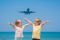 Two happy boys on the beach and a landing plane. Traveling with children concept.  royalty free stock photo