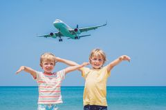 Two happy boys on the beach and a landing plane. Traveling with children concept.  royalty free stock photography