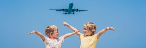 Two happy boys on the beach and a landing plane. Traveling with children concept BANNER, long format. Two happy boys on the beach and a landing plane. Traveling royalty free stock photo