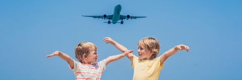 Two happy boys on the beach and a landing plane. Traveling with children concept BANNER, long format. Two happy boys on the beach and a landing plane. Traveling royalty free stock photos