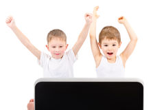 Two happy boys in front of a laptop screen royalty free stock photo