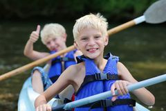 Two happy boys kayaking on the river. Active happy twin brothers, teenage school boys, having fun together enjoying adventurous experience kayaking on the river Royalty Free Stock Image