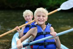 Two happy boys kayaking on the river. Active happy twin brothers, teenage school boys, having fun together enjoying adventurous experience kayaking on the river Royalty Free Stock Photography
