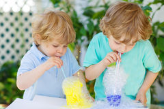 Two happy boys making experiment with colorful bubbles. Two little boys making experiment with colorful soap bubbles and water, outdoors stock images