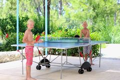 Two happy boys playing ping pong outdoors. Two happy boys, teenager twin brothers, enjoying summer vacation playing ping pong outdoors Royalty Free Stock Photos