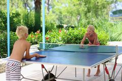 Two happy boys playing ping pong outdoors. Two happy boys, teenager twin brothers, enjoying summer vacation playing ping pong outdoors Royalty Free Stock Photo