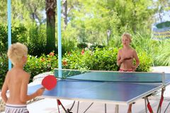 Two happy boys playing ping pong outdoors. Two happy boys, teenager twin brothers, enjoying summer vacation playing ping pong outdoors Royalty Free Stock Photography