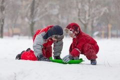 Two happy boys playing with slide on snowy landscape Stock Image