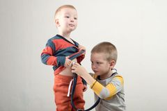 Two happy boys are playing with a stethoscope at home. Home doctor.  Stock Photos