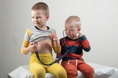 Two happy boys are playing with a stethoscope at home. Home doctor.  Stock Photography