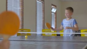 Two happy boys playing table tennis indoors. Brothers enjoying summer weekend with ping pong. happy children play sports games stock video footage