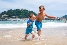 Two happy boys in running along a beach making big splashes royalty free stock images