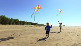 Two happy boys running with kites on the beach stock video