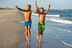 Two happy boys running on the sea beach at summer with raised ar Royalty Free Stock Images
