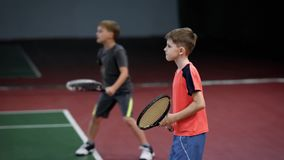 Two happy boys serving and returning balls on court with racket. Children hitting forehand in tennis having lesson. Two happy boys serving and returning balls stock video
