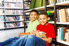 Two happy boys sitting on the floor in library Stock Images