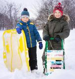 Two happy boys on sled and Skis in winter outdoors stock photos
