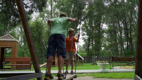 Two happy boys swinging on a swing set. Young boys swinging high on a big wooden swing set stock video footage
